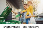 Small photo of Father Holding a Young Girl and Throw Away an Empty Bottle and Food Waste into the Trash. They Use Correct Garbage Bins Because This Family is Sorting Waste and Helping the Environment.
