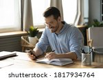 Small photo of Smiling young Caucasian man sit at desk at home office workplace look at cellphone screen watch webinar making notes. Happy millennial male use smartphone summarize plan writing in journal.