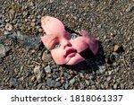 Old Broken Doll Face On Ground