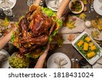 Top view of hands of young woman passing roasted turkey to her husband or other member of family over festive table served with homemade food