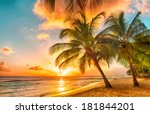 Stock photo beautiful sunset over the sea with a view at palms on the white beach on a caribbean island of 181844201