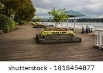 Quay in Pier Park at the riverfront of Fraser River in New Westminster City. Wood-covered promenade with flower beds  benches and and lounge chair against a background of cloudy sky