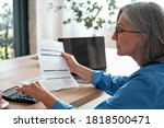 Small photo of Senior mature business woman holding paper bill using calculator, old lady managing account finances, calculating money budget tax, planning banking loan debt pension payment sit at home office table.