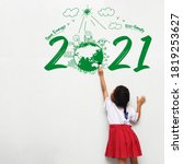Small photo of Little girl holding a paint brush painting creative environmental and eco-friendly, Save energy 2021 new year