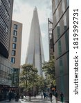 Small photo of London, UK - August 25, 2020: View of The Shard between the buildings on More London, people walking in front. The Shard is are one of the most popular landmarks in London.
