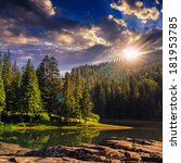 view on lake near the pine forest  on mountain background from rocky shore at sunset - stock photo