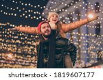 Small photo of Photo of positive couple having fun christmas x-mas around evening outside illumination boyfriend piggyback girlfriend holding hands fly