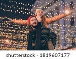 Small photo of Photo of positive couple having fun christmas x-mas around evening outside illumination boyfriend piggyback girlfriend holding hands fly