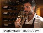 Small photo of Authentic shot of successful male sommelier is tasting a flavor and checking white wine quality poured in transparent glass in a wine cellar.