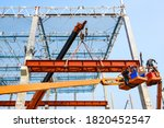 Construction workers installation steel structure girder runway beam lifting by mobile crane and placing on corbel of column concrete at the construction site project - stock photo