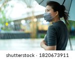 Small photo of asian female woman wearing face mask protection standing alone hand hold umbralle in raining season heavy raining outdoor street side