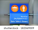 Sign in English and Arab at Dubai airport, indicating the way to the gents toilets and showers  - stock photo