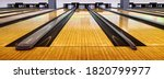 Small photo of Bowling wooden floor with lane, Generic Bowling Alley lanes with bowling ball going towards the pins.