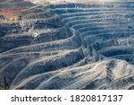 Small photo of Open-pit mining raw minerals for steel production. Giant iron ore quarry in Rudny, Kazakhstan. Yellow quarry truck down. Quarry steps under beauty sun.