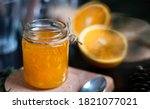 Small photo of Orange marmalade / orange jam in glass jar. A confiture is any fruit jam, marmalade, paste or fruit stewed in thick syrup. Orange marmalade & fruit jam in glass jar concept. Dark food photography.