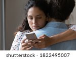 Small photo of Close up of bored young Caucasian woman hug man texting messaging with lover on smartphone online. Unhappy wife embrace husband cheating on web on cellphone. Family, relationship problem concept.