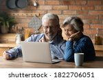 Small photo of Smiling mature 70s couple sit relax at table at home kitchen have fun shopping online on computer together. Smart modern happy senior man and woman look at laptop screen, pay with credit card o web.