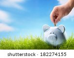 coin bank sitting on grass with ... | Shutterstock . vector #182274155