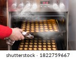 Small photo of Hand taking hot nutty cookies out of a steaming convection oven of kitchen stove. Fresh baked shortbread pastry in silicone baking molds on metal sheet pan. Crispy Xmas sweets in walnuts halves shape.