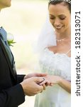 Groom Placing Ring On Brides...