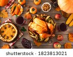 Small photo of Thanksgiving dinner with chicken, cranberry sauce, pumpkin pie, wine, seasonal vegetables and fruits on wooden table, top view. Traditional autumn holiday food concept.