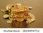 A metal toad next to a stack of coins. Symbol of happiness and financial success.