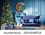 Small photo of Blue and silver Christmas interior. Living room with blue walls, blue sofa and silver and blue Christmas decorations on Christmas tree