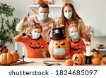 Small photo of Cheerful family in medical masks makes jack o lantern out of a pumpkin and scare for camera in cozy kitchen during Halloween celebration at home during the covid19 coronavirus pandemic