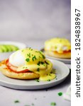 Small photo of Homemade Egg Benedict with perfect poached eggs Canadian bacon topped with Hollandaise sauce, selective focus