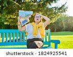 Small photo of Symptoms of menopause in mature woman, female waves newspaper to cool off, feels hot, age hormonal changes. Woman on bench in the park