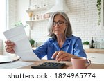 Small photo of Senior mature business woman holding paper bill using calculator, old lady managing account finance, calculating money budget tax, planning banking loan debt pension payment sit at home kitchen table.