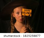 Small photo of Little pretty girl witch in black wizard hat holds greeting Happy Halloween card and says Boo. Child dressed in ghost party costume scarily staring at camera. Festive autumn holidays celebration.