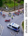 Small photo of PONTEVEDRA, SPAIN - AUGUST 18, 2019: A local police van controls the traffic while passing a platoon of cyclists in a sports event.