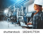 Small photo of Engineer woman with laptop inspect modern industrial gas boiler room. Heating gas boilers, pipelines, valves. Blue toning with sunflare. Mixed media