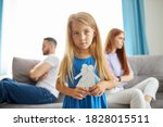 Small photo of sweet little caucasian child girl holding family picture drawing feeling upset about parents divorce, innocent sensitive little kid suffer from trauma offended by fights conflicts shared custody