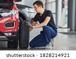 Man in uniform changing tire of automobile. Conception of car service. - stock photo