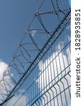 Small photo of High fence with barbed wire. Against the blue sky. The barrier is metal. Passage is forbidden. Restricted area. Protected area. Sharp iron spikes. Steel fence. Insurmountable barrier.