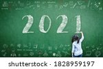 Small photo of 2021 Happy new year school class academic calendar with student kid's hand drawing greeting on teacher's green chalkboard for educational celebration, back to school, STEM education classroom schedule