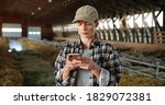 Small photo of Young Caucasian woman using smartphone and working in farm stable. Female farmer tapping and scrolling on mobile phone in shed. Shepherd texting message on telephone. Farming concept.