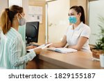 Female receptionist taking application form from her customer at health spa check in counter. They are wearing protective face masks due to COVID-19 pandemic.