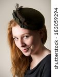 Small photo of Redhead smiling cheekily in green feathered hat