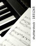 Piano keys and sheet music. - stock photo