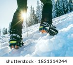 Small photo of Close up shot of mountain boots with crampons and snow gaiters with backlight sun beams and snowy spruces on background . High mountaineer pounding boots in hard snow ascending UP on the summit.