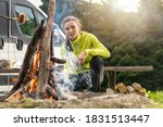 Young Caucasian Woman Grilling Polish Sausage on Campfire Flames While on RV Motorhome Camping. Recreational Vehicle Camper Van Class B in Background. - stock photo