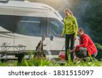Recreational Vehicle RV Park Pitch and Caucasian Couple Making Campfire and Grilling Some Food Having Fun. Summer Vacation Wilderness Destination. - stock photo