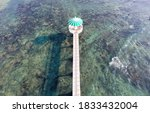 Small photo of Aerial view of a gazebo standing over the seawater and connected by a bridge to the shore on a sunny summer day, in Xiaochijiao, Xiyu Township, Penghu, Taiwan