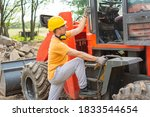 Friendly construction worker with his excavator. Handsome male  construction worker climbs on a construction machine - stock photo