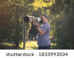 wildlife photographer using telephoto lens with camouflage coating photographing wild life using gimbal head on tripod. professional photography equipment for cinematic shooting in the nature outdoor - stock photo