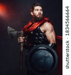 Small photo of Warlike and armoured rome empire fighter with beard and muscular build posing holding shield and axe in dark room with spotlight.
