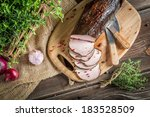 Fresh smoked ham in the pantry with herbs - stock photo
